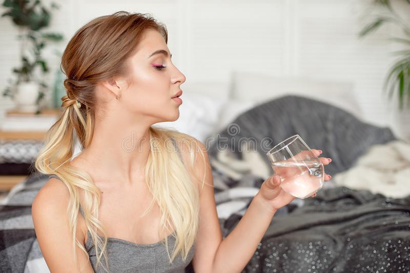 Caucasian girl drinks water sitting on the bed in the morning.  royalty free stock photo