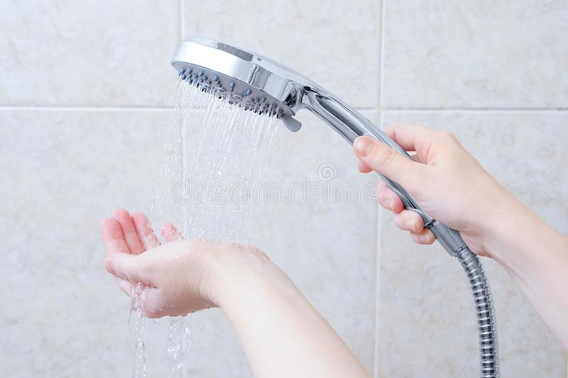 Caucasian girl holding a shower watering can. Jets of water on hand. Background beige tile royalty free stock photography