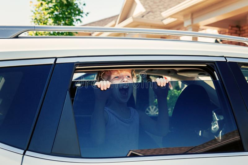 Caucasian girl left alone in car during hot sunny day. Child crying screaming trying to get out of closed vehicle stock photo