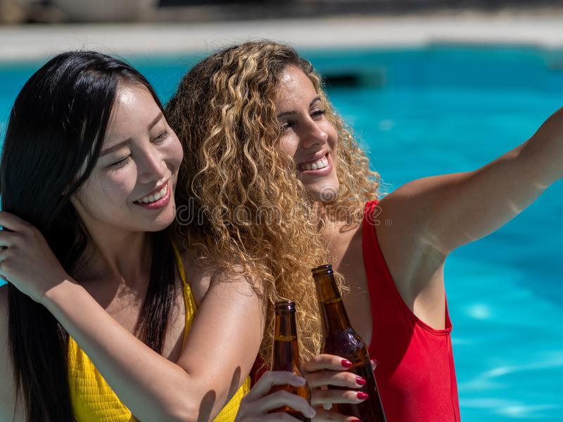 Caucasian girl and oriental girl play and laugh in the pool, drinking beer.  stock photo