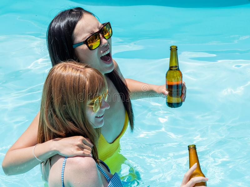 Caucasian girl and oriental girl play and laugh in the pool, drinking beer.  royalty free stock photography