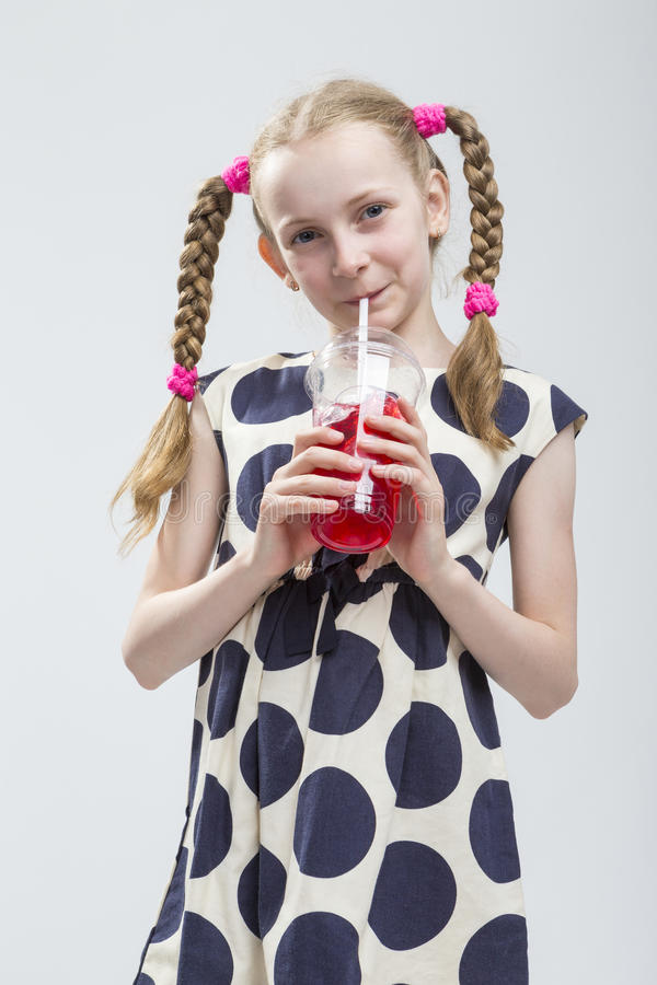 Caucasian Girl With Pigtails Standing in Polka Dot Dress with Cup of Red Juice. royalty free stock image