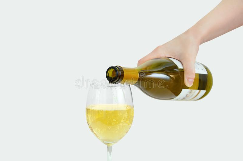 Caucasian girl pours wine from a bottle into glass. Close-up. Gray background. Caucasian girl pours wine from a bottle into a glass. Close-up. Gray background royalty free stock photo