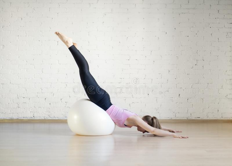 Caucasian girl practice pilates with big fit ball in fitness studio, upside down pose, selective focus. Yoga, workout, stretching, balance, exercise therapy stock photos