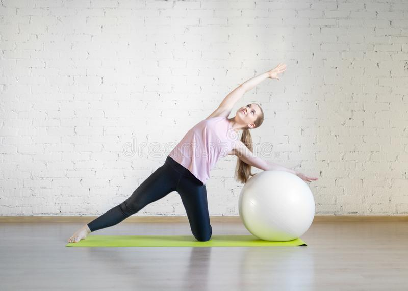 Caucasian girl practise pilates with big fit ball, attractive posing in fitness studio, lifestyle, selective focus. royalty free stock photo