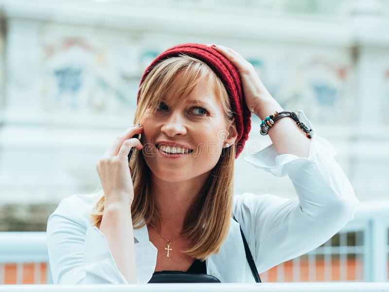 Caucasian girl with red beret and white shirt, she talks on the phone with her smartphone.  royalty free stock photography