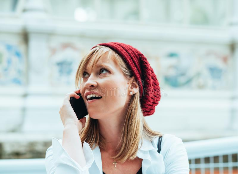 Caucasian girl with red beret and white shirt, she talks on the phone with her smartphone.  stock image