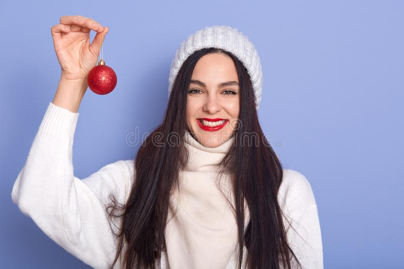 Caucasian girl with red christmas ball in hands, stands smiling isolated over blue background, brunette female wearing warm white stock photography