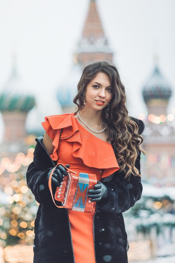 Caucasian girl in a red dress plays on an accordion in the winter a blizzard against the background of St. Basil` stock images