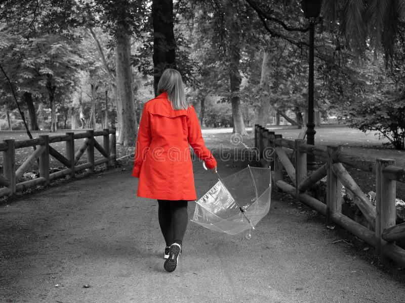 A Caucasian girl with a red gabardine walks through a park with a transparent umbrella in her hand royalty free stock images