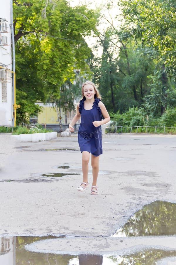 Caucasian girl run in summer. Cute running European girl with disheveled hair stock photography