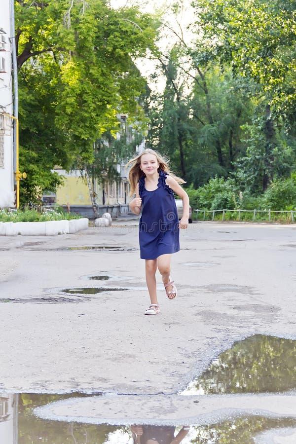 Caucasian girl run in summer with disheveled hair. Cute running European girl with disheveled hair stock photo