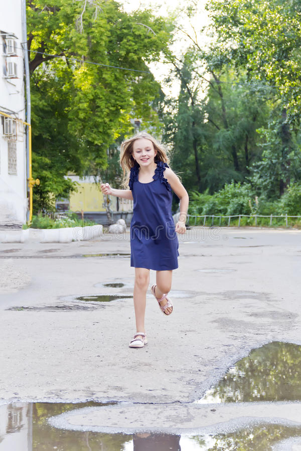 Caucasian girl run in summer with disheveled hair. Cute running European girl with disheveled hair royalty free stock images
