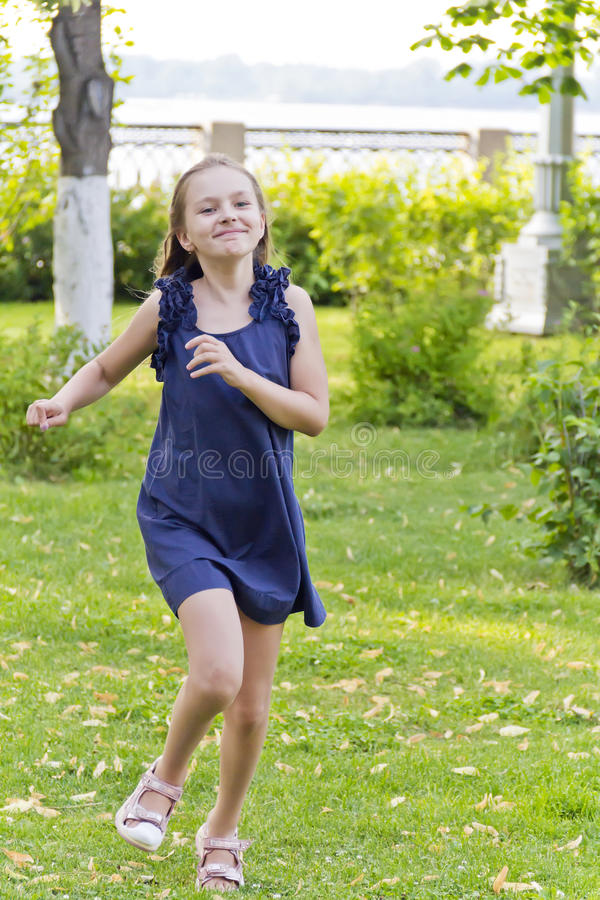 Caucasian girl run in summer with disheveled hair. Cute running European girl with disheveled hair in green park stock photography