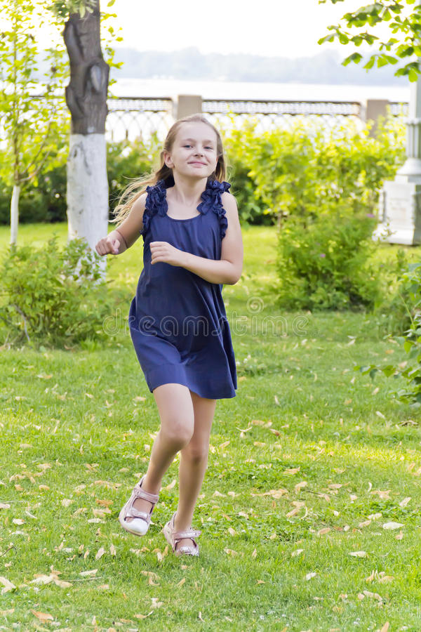 Caucasian girl run in summer with disheveled hair. Cute running girl with disheveled hair in green park royalty free stock photography