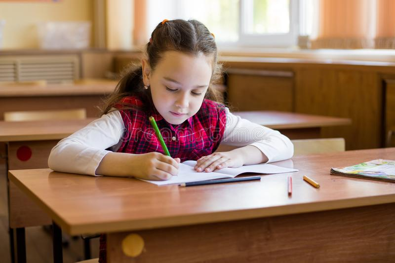Caucasian girl sitting at desk in class room and begins to carefully draw in a pure notebook. Preparation for exams.  stock image