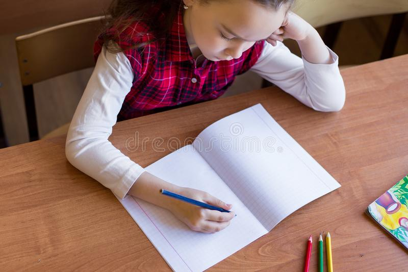 Caucasian girl sitting at desk in class room and begins to draw in a pure notebook. Preparation for exams, tests.  stock image