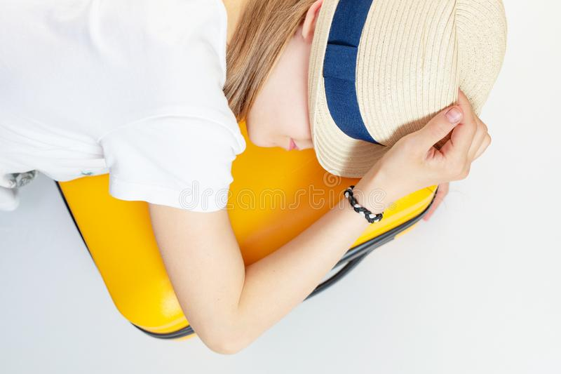 Caucasian girl teenager in a hat lies on a suitcase, tired of waiting. Vacation, summer camp, travel, trip stock image