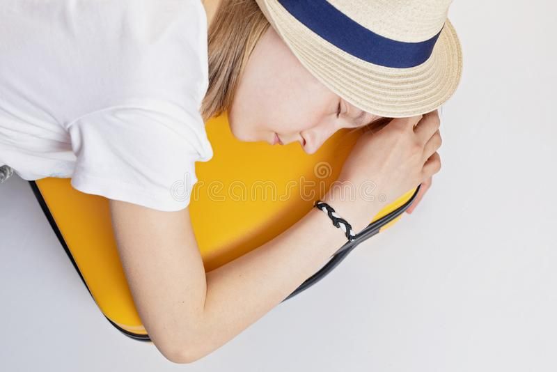 Caucasian girl teenager in a hat lies on a suitcase, tired of waiting. Vacation, summer vacation, travel royalty free stock images