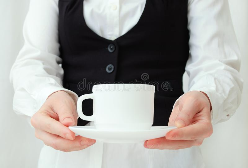 Caucasian girl waiter in white shirt and black vest with tea pair in hands royalty free stock images