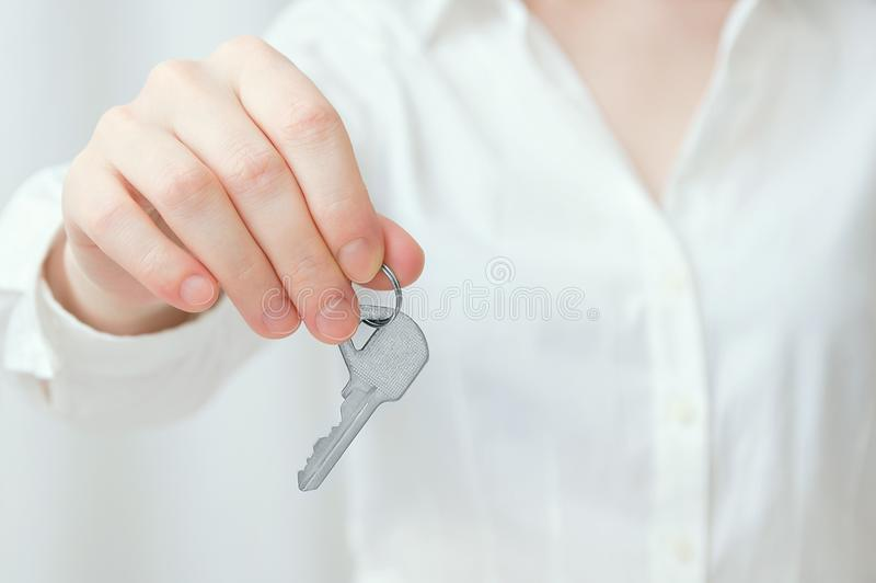 Caucasian girl in white shirt holds key in hand stock photography