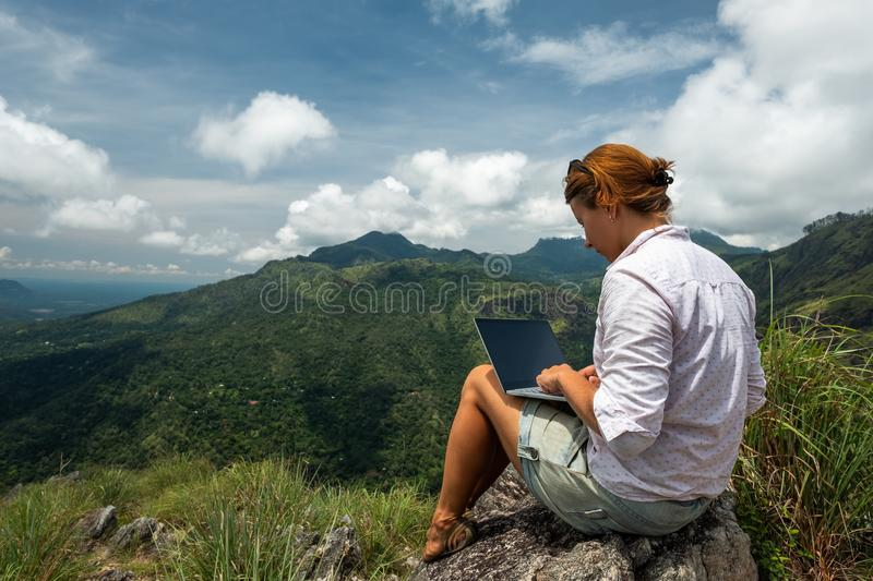 Girl working on her computer on the top of the mountain. Caucasian girl working on her computer on the top of the mountain. Concept or remote work in internet stock photos