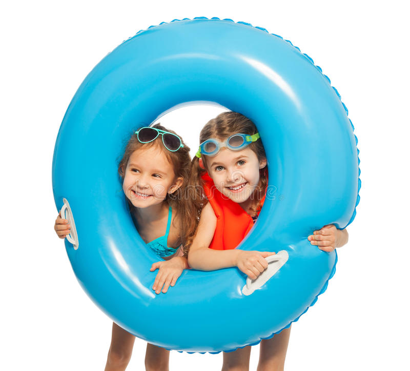 Caucasian girls looking out big blue rubber ring. Two smiling swimmers looking out big blue rubber ring holding it in their hands royalty free stock image