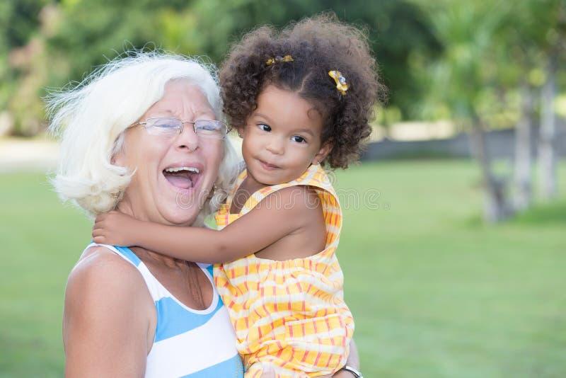 Caucasian grandma carrying her hispanic granddaughter stock photos
