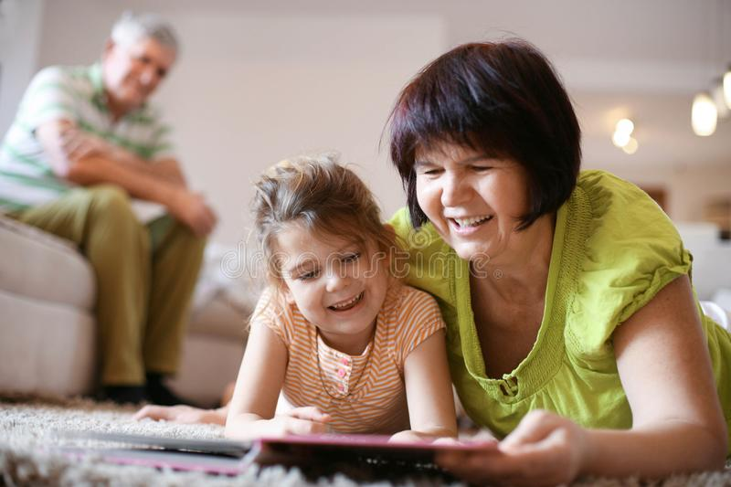 Caucasian grandmother reading book to granddaughter. stock photography