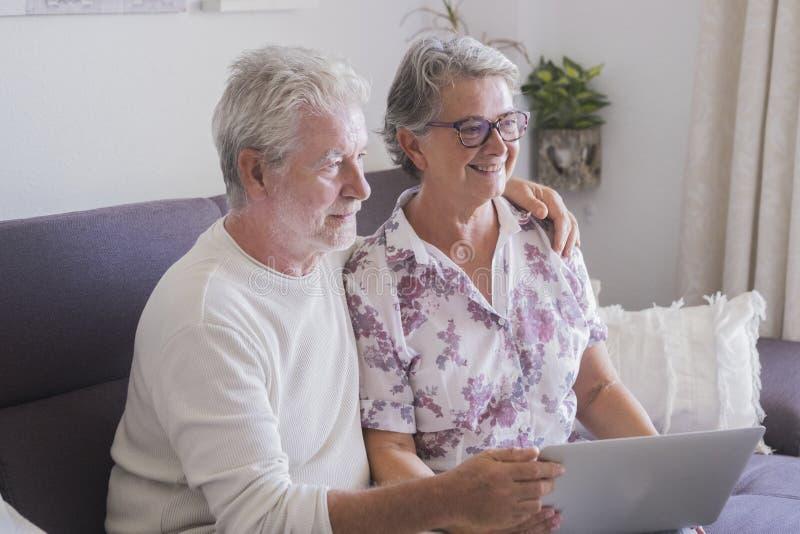 Caucasian härliga par av den äldre höga vuxna människan hemma som tillsammans använder internet med en internet för bärbar dator  royaltyfri fotografi