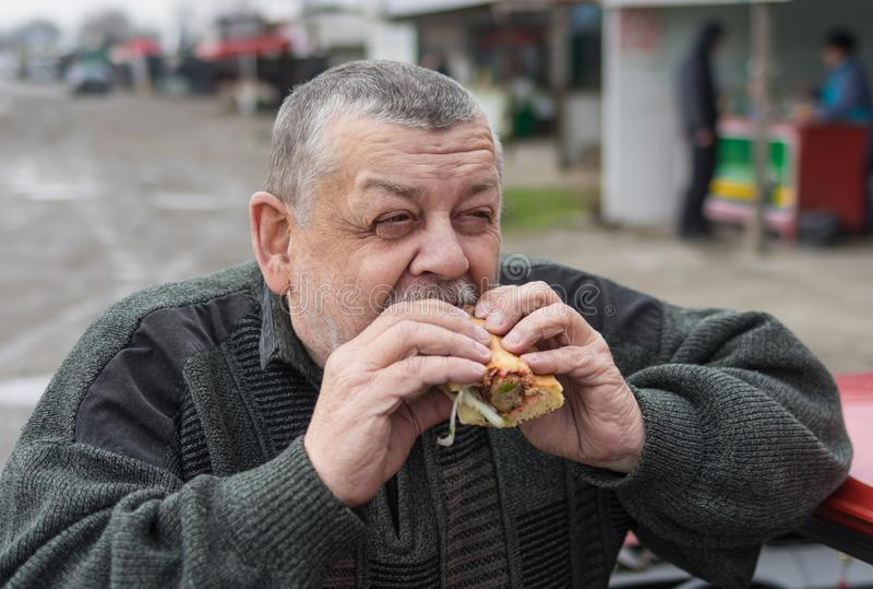 Caucasian hög chaufför som äter lyulyakebab i lavash royaltyfri foto