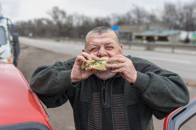 Caucasian hög chaufför som äter lyulyakebab i lavash nära hans bil royaltyfri bild