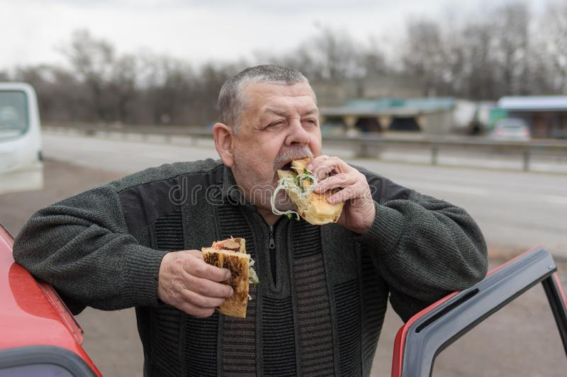 Caucasian hög chaufför som glufsar lyulyakebab i lavash nära hans bil arkivbilder