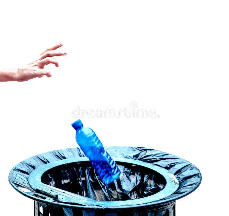 Caucasian hand throwing a bottle of water made of blue plastic into a wastepaper basket.  stock photo