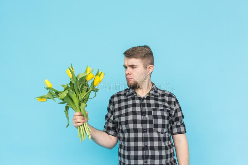 Caucasian handsome man with bunch of yellow tulips on blue background. stock image