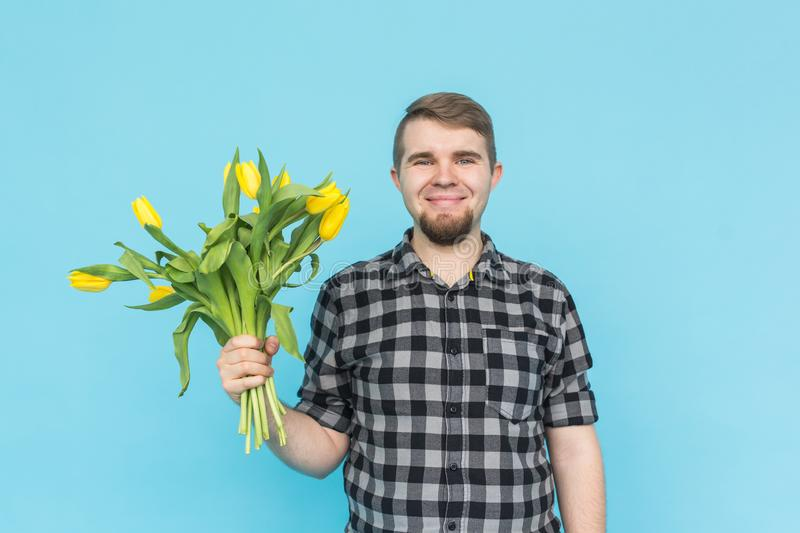 Caucasian handsome man with bunch of yellow tulips on blue background. royalty free stock images