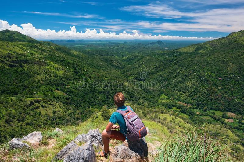Caucasian hiker man take a rest on mountain peak with backpack. stock photos