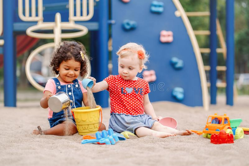 Caucasian and hispanic latin babies children sitting in sandbox playing with plastic colorful toys. Sandy ground. Two cute Caucasian and hispanic latin babies royalty free stock images