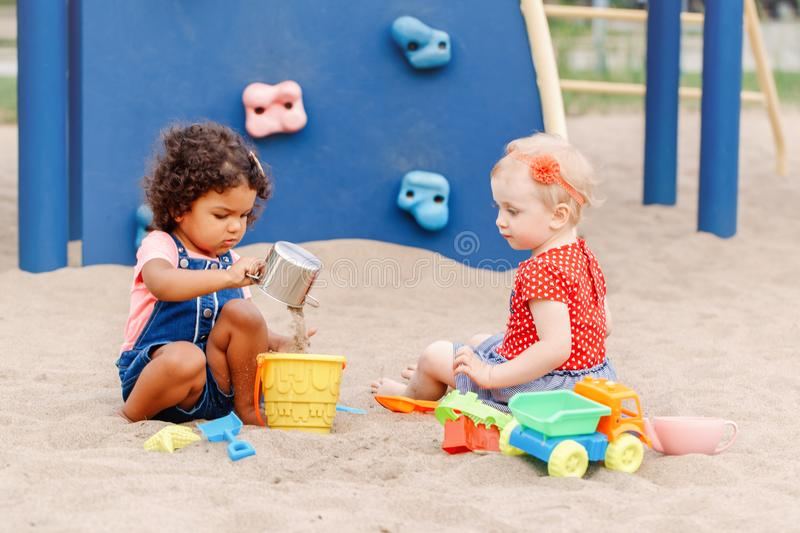 Caucasian and hispanic latin babies children sitting in sandbox playing with plastic colorful toys. Show me how to do it. Two cute Caucasian and hispanic latin royalty free stock photo