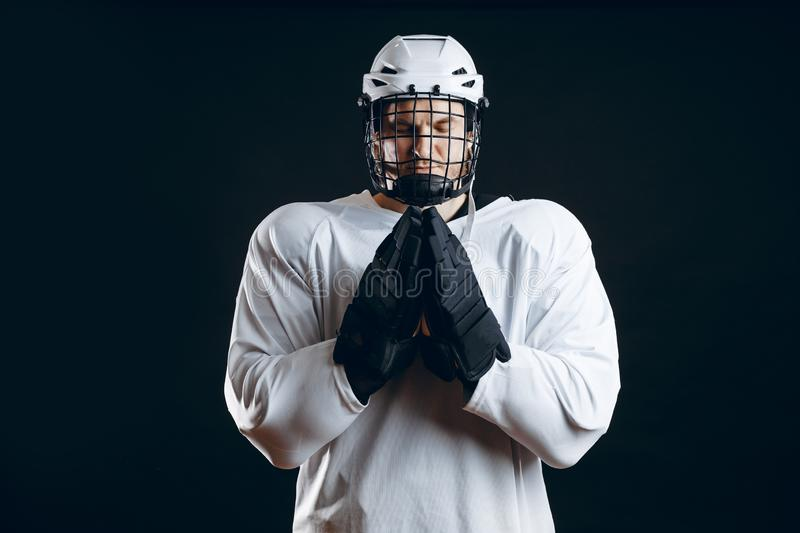 Caucasian hockey player, in uniform, isolated on black, prays for good luck. royalty free stock image
