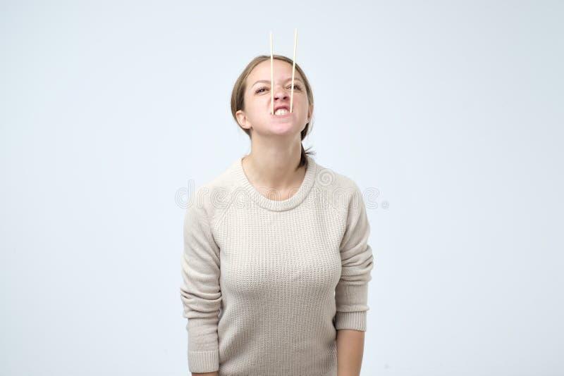 Caucasian hungriga pinnar för flickainnehavsushi som långa tänder i hennes mun royaltyfri fotografi