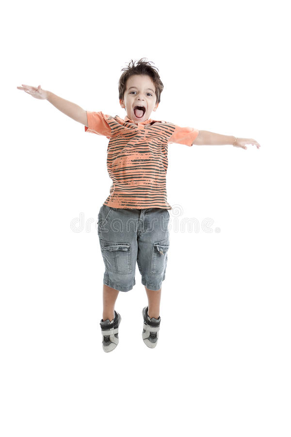 Caucasian kid jumping wearing an orange t shirt. A nice brazilian and caucasian kid jumping in the air, wearing a nice orange t shirt, short jeans and tennis royalty free stock images
