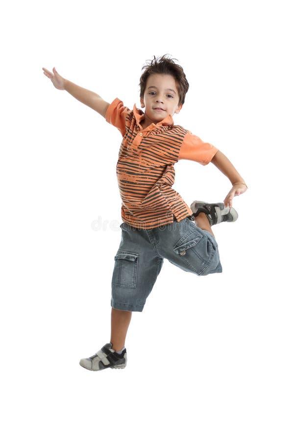 Caucasian kid jumping wearing an orange t shirt. A nice brazilian and caucasian kid jumping in the air, wearing a nice orange t shirt, short jeans and tennis royalty free stock photos