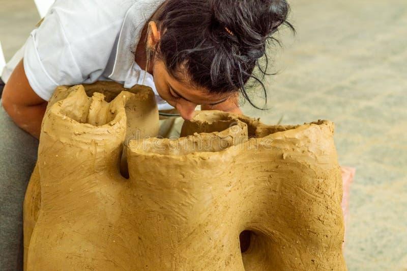 Caucasian konstnär för härlig brunett som arbetar på en skulptur i en atelier royaltyfria bilder