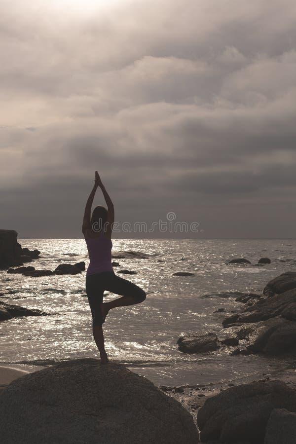 Caucasian kvinna att utföra yoga på stranden royaltyfri foto