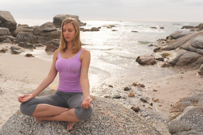 Caucasian kvinna att utföra yoga på stranden royaltyfri bild