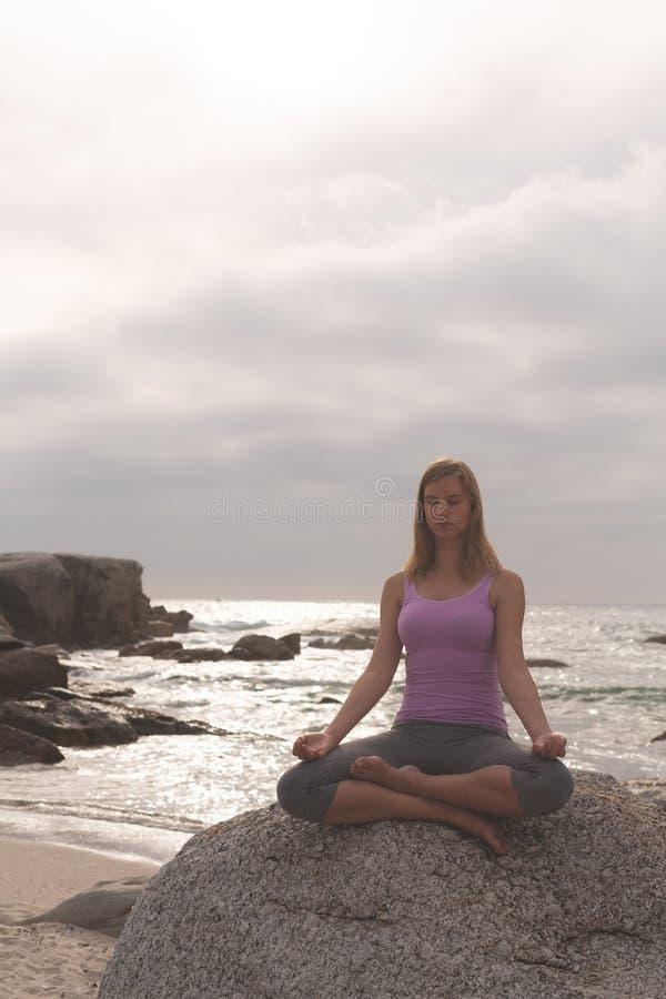 Caucasian kvinna att utföra yoga på stranden royaltyfria bilder