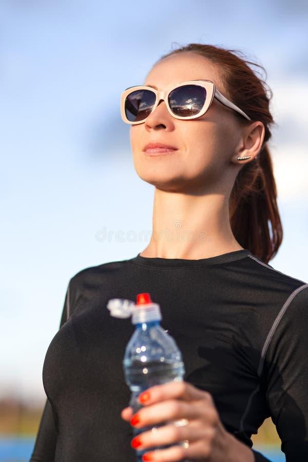 Caucasian kvinna f?r kondition i Sportwear och solglas?gon med vatten fr?n flaskdet fria royaltyfria foton