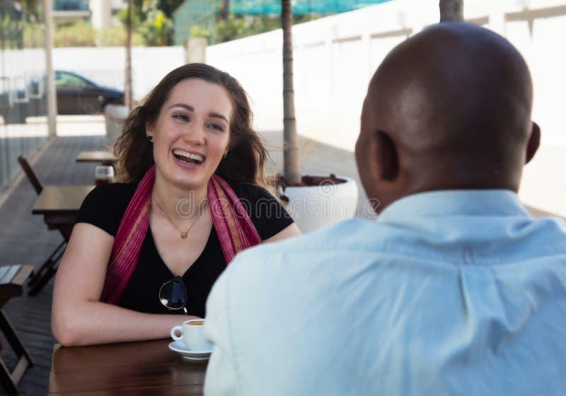 Caucasian kvinna med brunetthår som talar med afrikansk amerikanmannen royaltyfria bilder