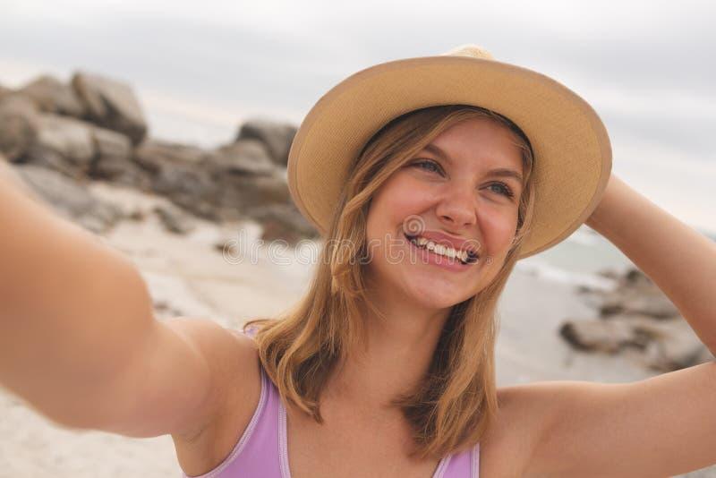 Caucasian kvinna med hattanseende på stranden royaltyfria foton